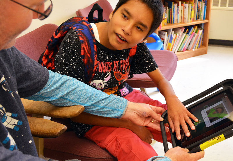 Young boy using assistive technology in therapy