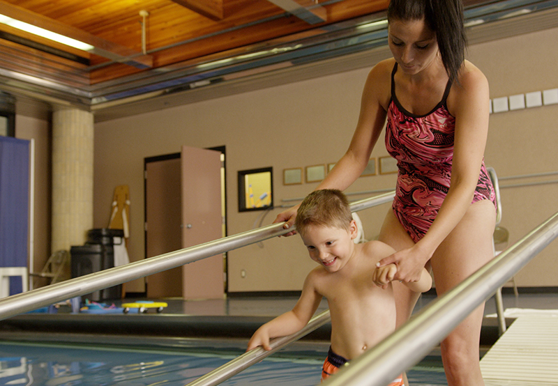 Young boy entering pool for Physical Therapy at Anne Carlsen