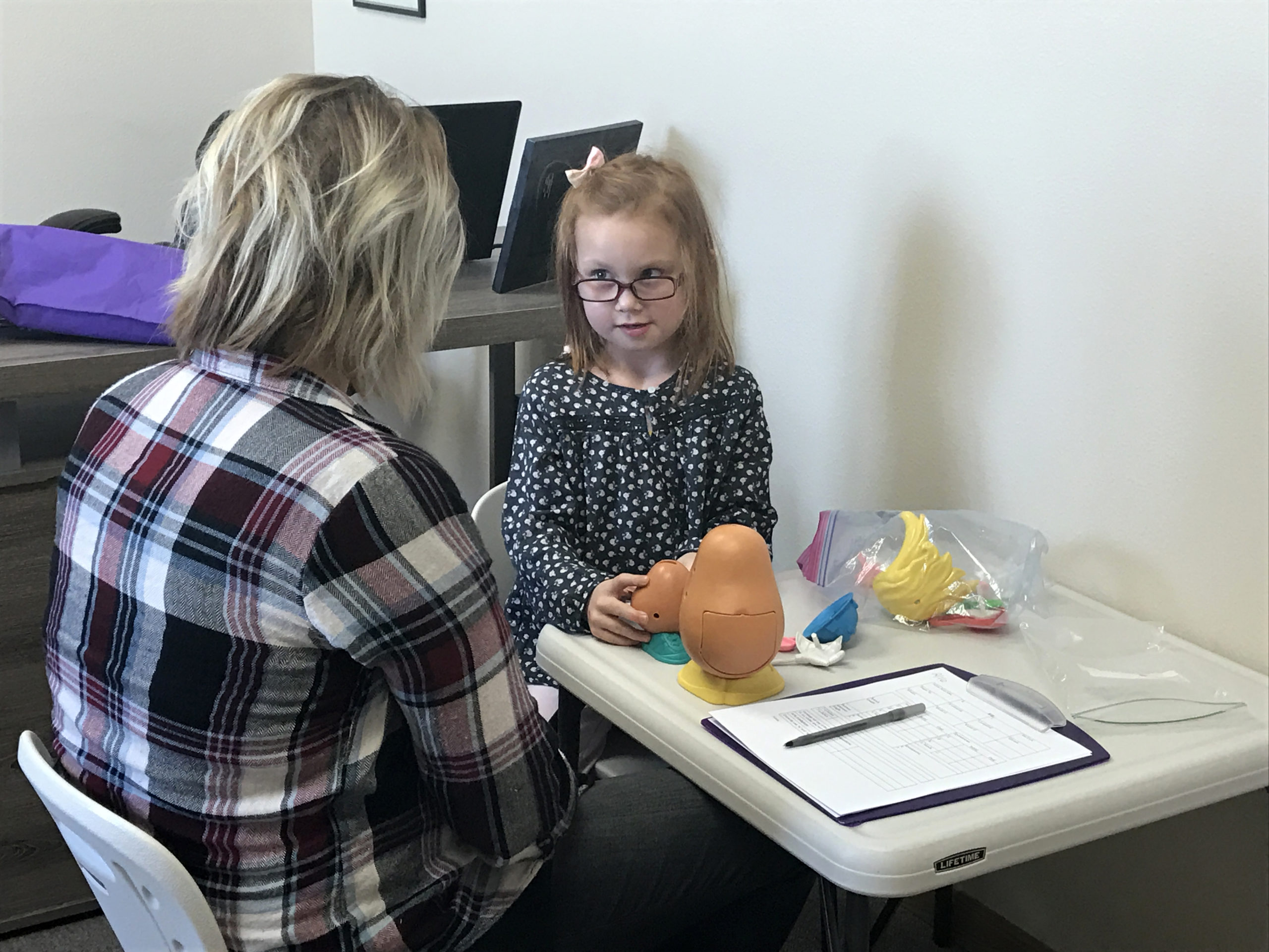 Young girl using Potato Head in speech therapy session